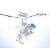 Botella de chapoteo del agua en el fondo blanco Imagen de archivo libre de regalías