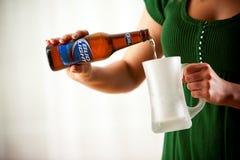 Botella de colada de la mujer de Bud Light Into Mug Bud Light Is Produce Foto de archivo libre de regalías