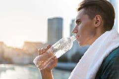 Botella de consumición del atleta de sexo masculino sereno de agua Fotografía de archivo