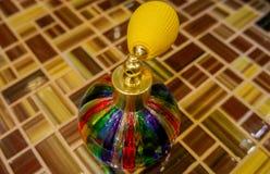 Botella de cristal coloreada del espray en superficie tejada fotografía de archivo