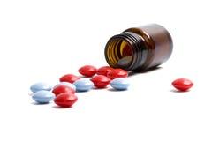 Botella de cristal con las píldoras rojas y azules Imagenes de archivo