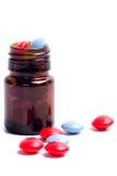 Botella de cristal con las píldoras rojas y azules Imágenes de archivo libres de regalías