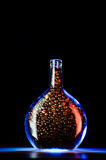 Botella de cristal con los granos de café en luz azul Fotos de archivo libres de regalías