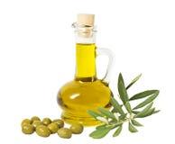 Botella de cristal de aceite de oliva superior y de algunas aceitunas con una rama aislada Fotos de archivo