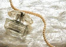 Botella de cristal de perfume femenino en el fondo de plata con los accesorios Fotografía de archivo
