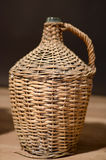 botella de cristal para el rakia protegido por la malla de madera imagenes de archivo