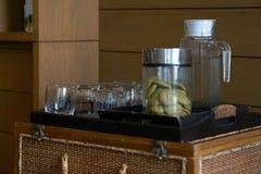 Botella de cristal, taza y galletas en tarro en la bandeja de madera para la porción imagen de archivo