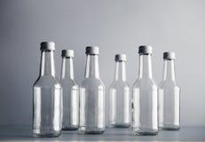 Botella de cristal vacía del cocoktail con el sistema blanco de la maqueta del casquillo Imagen de archivo libre de regalías
