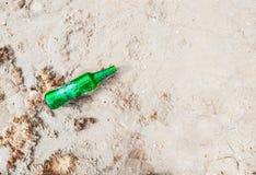 Botella de cristal vacía verde en las arenas fotos de archivo libres de regalías