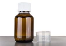 Botella de jarabe de la tos y de capacidad volumétrica Fotos de archivo libres de regalías