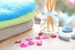 Botella de lámina del difusor del Aromatherapy en una tabla de madera con las toallas, los pétalos y las piedras del masaje imagenes de archivo