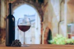 Botella de la copa de vino roja y de vino rojo en el backgroung del lagar Fotos de archivo