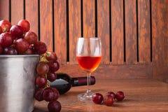 Botella de la copa de vino y de vino con las uvas rojas en fondo de madera imagenes de archivo