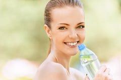 Botella de la explotación agrícola de la mujer joven de agua Imagen de archivo