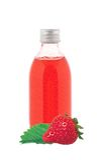 Botella de la medicina con el jarabe rojo y la fresa aislados en blanco Foto de archivo