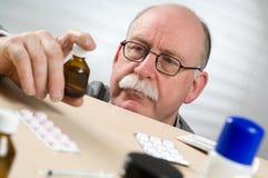 Botella de la medicina de la cosecha del hombre mayor Imagen de archivo libre de regalías