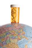 Botella de la medicina en un globo de la tierra Imagen de archivo
