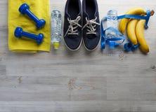 Botella de la toalla de las pesas de gimnasia de las zapatillas de deporte de agua y de plátanos Fotos de archivo