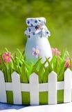 Botella de leche en cesta decorativa con las flores Fotografía de archivo libre de regalías