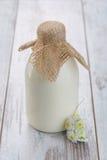 Botella de leche que se coloca en la tabla Imágenes de archivo libres de regalías