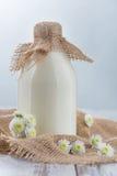 Botella de leche que se coloca en la tabla Imagen de archivo