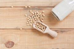 Botella de leche de soja y de habas de la soja en el fondo de madera Fotografía de archivo