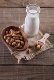 Botella de leche y de nueces de la almendra sobre fondo de madera rústico fotos de archivo