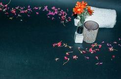 Botella de loción del cuerpo con las flores, las flores del pétalo y las toallas Foto de archivo libre de regalías