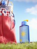 Botella de loción y de bolso del bronceado con los artículos de la playa en primer de la hierba Foto de archivo