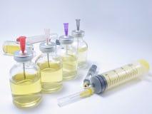 Botella de medicina y de una jeringuilla grande imagen de archivo libre de regalías