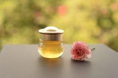 Botella de miel con la rosa del rosa Fotografía de archivo libre de regalías