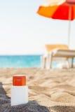 Botella de nata del bloque del sol en sombra en la playa Imágenes de archivo libres de regalías
