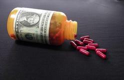 Botella de píldora con la escritura del dólar Imagen de archivo