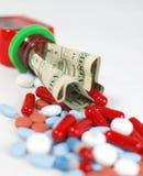 Botella de píldora con los dólares Fotografía de archivo libre de regalías