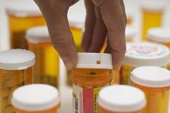 Botella de píldora de la abertura de la mano Imagen de archivo libre de regalías