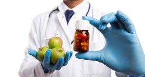 Botella de píldora de la dieta sostenida por el doctor y las manzanas en la otra mano imágenes de archivo libres de regalías