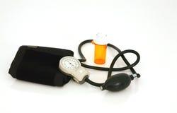 Botella de píldora vacía con el manómetro de la presión arterial Imágenes de archivo libres de regalías