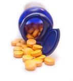 Botella de píldoras anaranjadas aisladas en blanco Foto de archivo libre de regalías