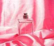 Botella de perfume aislada en rosa Fotos de archivo