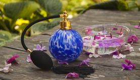 Botella de perfume azul de cristal del vintage y fondo de madera de las flores imagen de archivo libre de regalías