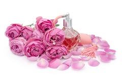Botella de perfume con el collar de oro entre las flores en el fondo blanco Perfumería, cosméticos, colección de la fragancia foto de archivo