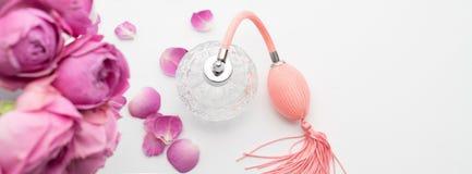 Botella de perfume con las flores en el fondo blanco Perfumería, cosméticos, colección de la fragancia Copyspace para el texto foto de archivo libre de regalías