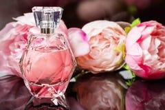 Botella de perfume con las flores en fondo oscuro Perfumería, cosméticos, colección de la fragancia imagenes de archivo