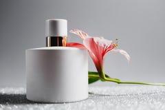 Botella de perfume con las flores rosadas Imagen de archivo libre de regalías