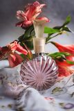 Botella de perfume con las flores rosadas Fotografía de archivo libre de regalías