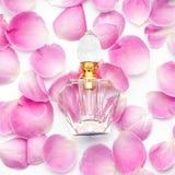 Botella de perfume con los pétalos de la flor en el fondo blanco Perfumería, cosméticos, colección de la fragancia imagenes de archivo