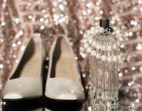Botella de perfume con los zapatos y los pendientes Foto de archivo libre de regalías