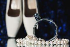 Botella de perfume con los zapatos y los pendientes Fotografía de archivo libre de regalías