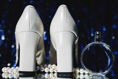 Botella de perfume con los zapatos y los pendientes Fotos de archivo