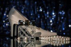 Botella de perfume con los zapatos y los pendientes Fotografía de archivo